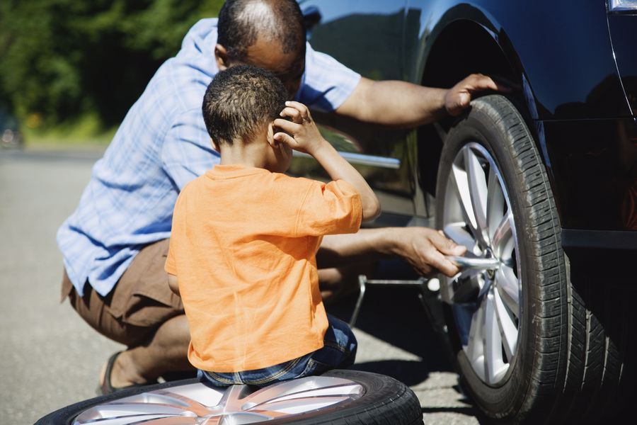 Father and son changing their car tire