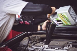 Man pouring a bottle of motor oil in a car engine